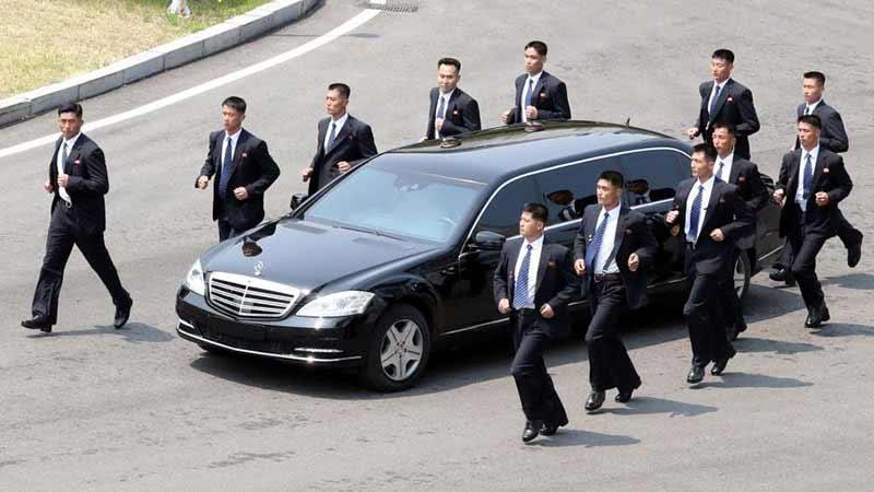 Ochranka Kima Jong-una, která v sáčku a kravatách kluše vedle opancéřované limuzíny